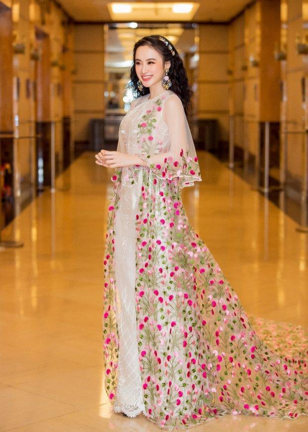 """Khẳng định vị thế """"nữ hoàng thảm đỏ"""", Angela Phương Trinh ghi dấu ấn khi tham dự sự kiện với chiếc đầm thêu hoa rơi nhẹ nhàng. Phần tà dài cùng mái tóc uốn xoăn góp phần đem lại vẻ nữ tính cho """"Bà mẹ nhí""""."""