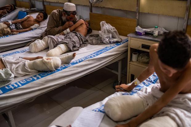 Ông Hamisha Gul đang vỗ về con trai Abdul Rashid trên giường bệnh. Ảnh: New York Times