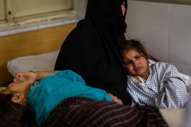 Lol Pora vỗ về cháu gái Rabia, 7 tuổi, và Marwa, 4 tuổi. Marwa mất mẹ và em gái sinh đôi sau vụ nổ. Ảnh: New York Times