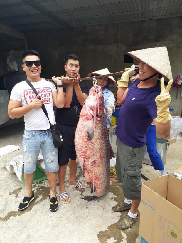 Nhiều người thích thú cùng con cá trắm đen hơn 60 kg. Ảnh: Đức Sơn.