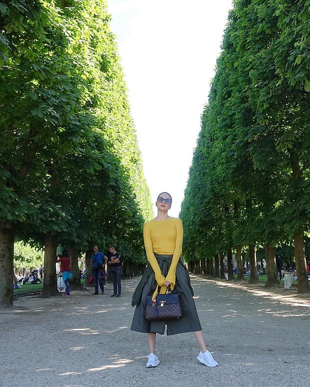 Đang tung tăng tại Paris, Thiều Bảo Trang ưu ái chọn lựa áo dài tay tông vàng mustard phối cùng quần culottes. Chiếc túi Louis Vuitton đắt giá mà cô nàng đang cầm trên tay góp phần khiến set đồ tăng thêm vẻ sành điệu.