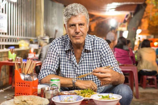"""Tuy nhiên, đối với những người yêu ẩm thực quốc tế, ông Bourdain không phải cái tên xa lạ. Ông từng là bếp trưởng nổi danh, tác giả từng khiến thế giới ẩm thực lên cơn sốt với cuốn sách Kitchen Confidential và là nhân vật được yêu thích trong các show truyền hình về ẩm thực như """"Anthony Bourdain: Parts Unknown"""". Đặc biệt hơn cả, ôngBourdain là một người """"nặng tình, nặng nghĩa"""" với ẩm thực Việt Nam.Trong bài phỏng vấn trên chuyên trang du lịch Condé Nast Traveler hồi năm 2014, ông Bourdain cho biết: """"Chuyến đi tới Việt Nam đã thay đổi cuộc đời tôi.Có lẽ bởi tất cả quá đỗi mới mẻ và khác với cuộc đời trước đó của tôi, cũng như thế giới tôi lớn lên. Ẩm thực, văn hóa, cảnh quan và cả mùi vị, chúng đều không thể tách rời. Nó như thể một hành tinh khác, một hành tinh ngon lành đã kéo tôi vào và không bao giờ buông ra"""".Trong ảnh,Bourdain thưởng thức món cơm hến trên đường phố ở Huế. Với món bún bò Huế, ông gọi đây là""""món súp ngon nhất thế giới""""."""