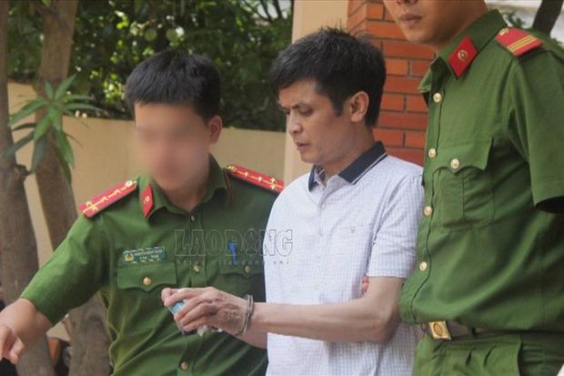 Cảnh sát dẫn giải Nguyễn Đình Lê ra xe sau khi kết thúc phiên tòa xét xử (Ảnh: Lao động)