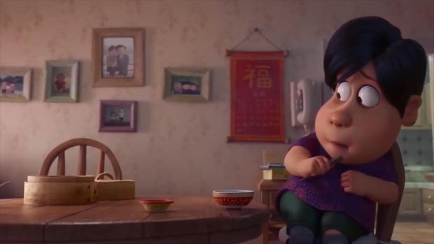 """Căn nhà mang màu sắc ấm áp, trên bàn ăn có chén, đũa, xửng, trên tường thì treo ảnh gia đình, còn có treo chữ """"Phúc"""" tượng trưng cho hạnh phúc, ấm no."""
