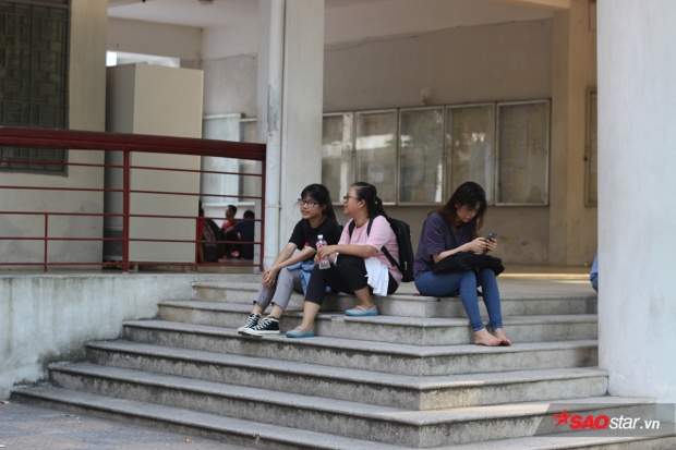 Một số bạn sinh viên ra sảnh lớn của trường đại học ngồi cho thoáng mát.