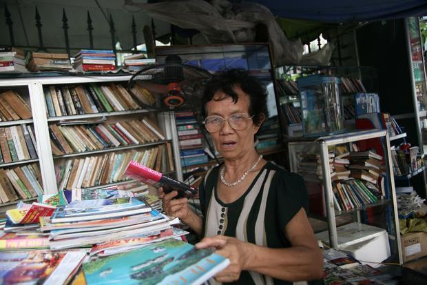 Bà Dung bên kệ báo miễn phí của mình.