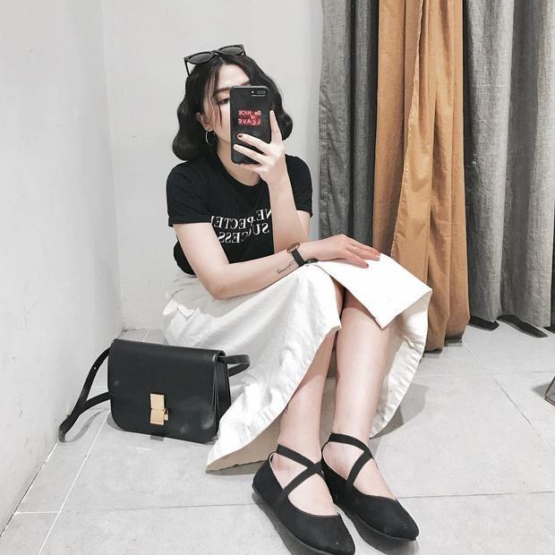 Heo Mi Nhon vô cùng trẻ trung nhưng không hề đơn điệu với cách mix đồ cơ bản cùng combo áo phông chữ và váy midi. Cô nàng khéo léo xỏ chân vào đôi búp bê đan quai chéo để tạo điểm nhấn cho set đồ.