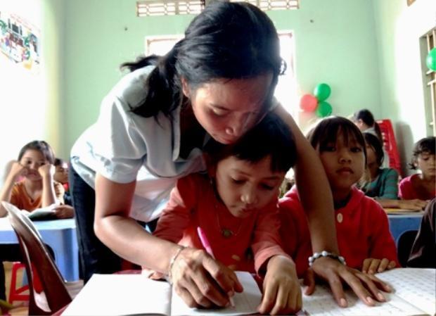 Rmah B'Blao uốn nét chữ cho học sinh. Ảnh: Việt Hiến.