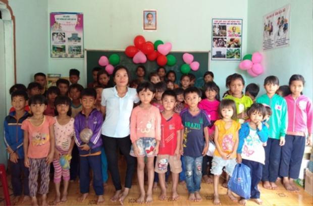 Cô giáo B'Lao (áo trắng) đứng trên đôi chân co quắp cùng các học trò. Ảnh: Việt Hiến.
