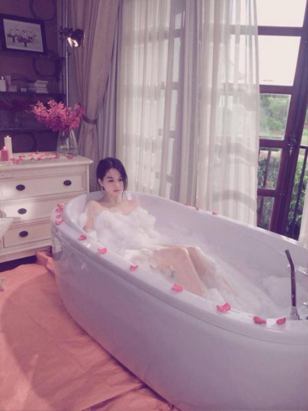 Ngọc Trinh gợi cảm trong chiếc bồn tắm màu trắng được đặt trong phòng, gần ban công. Có vẻ đây là không gian chụp hình của nữ người mẫu này.