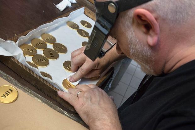 Chiếc huy chương vàng được kiểm tra kỹ lưỡng và làm sạch bằng cồn trong khâu cuối cùng.