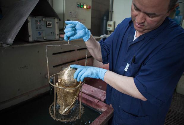 Người thợ đem tẩy rửa dầu mỡ bám trên chiếc cúp.