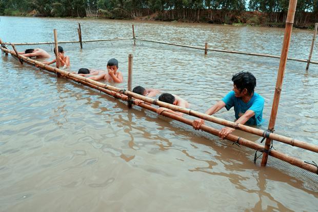 Không ngại khó nhọc dù đã ở tuổi 66, bà Thia tự tổ chức các lớp dạy bơi ngay trên sông cho trẻ con trong xóm. Hồ bơi của bà là những chiếc cọc tre đóng chặt xuống đáy sông, được bao lưới cẩn thận xung quanh, chiều ngang độ 4m, dài 8m và cao 2m. Mỗi ngày, trước khi học sinh đến, bà phải ngâm mình dưới nước cả tiếng đồng hồ để dựng hồ bơi.