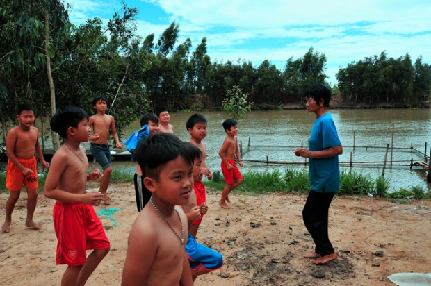 Trước mỗi giờ học, bà Sáu cho các em xếp thành hàng trên bờ sông. Rất bài bản, bà cho các em khởi động, làm nóng cơ thể, sau khoảng 20 phút các em mới xuống hồ.