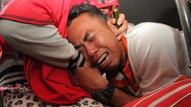 Người thân nạn nhân khóc ngất tại hiện trường. Ảnh: AFP.