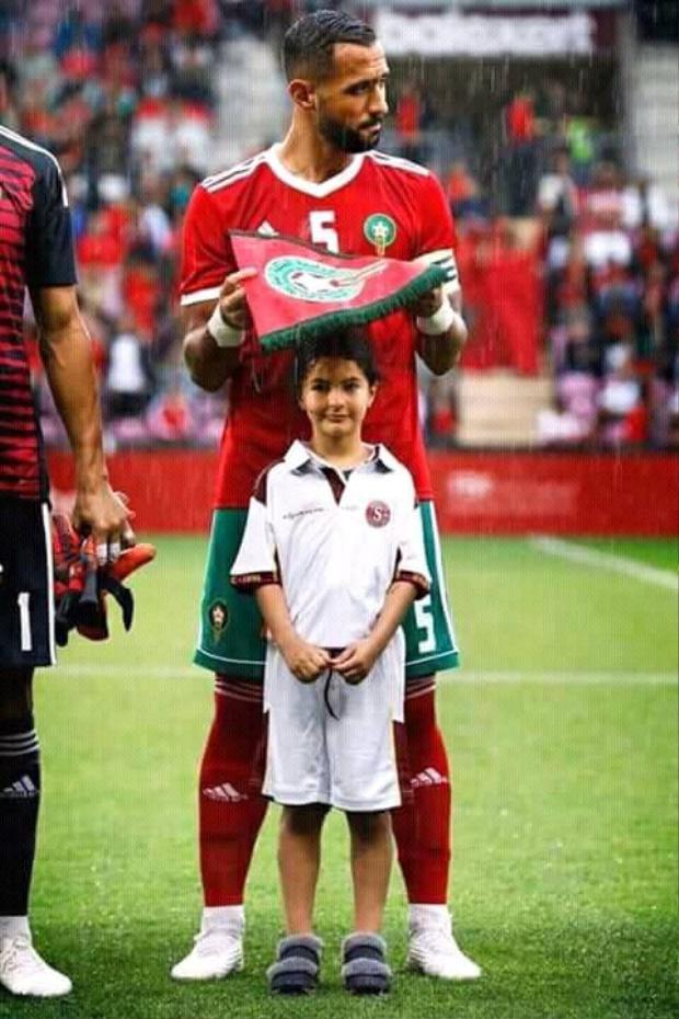 Medhi Benatia (Morocco) dùng cờ hiệu che mưa cho bé gái trên sân cỏ. Ảnh: Ảnh: Twitter.