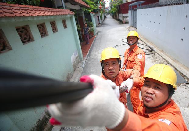 Trong ảnh, nhóm công nhân của Công ty Điện lực Long Biên, trực thuộc EVN HANOI đang đi kéo dây tăng cường truyền tải tại một tổ dân phố thuộc địa bàn phường Việt Hưng vào ngày 18/6/2018. Đây là một trong số các công việc hàng ngày các anh phải làm trong những ngày trời nắng gắt.