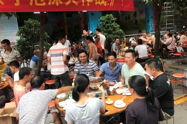 Một nhóm người ăn thịt chó bên ngoài một trường mẫu giáo trong lễ hội thịt chó tại địa phương.