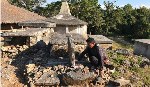 Anh Yusuf Djanggambolu, 44 tuổi đến thăm mộ của mẹ mình, được đặt trước nhà ông Umbo Mbora tại làng Lewa. Ảnh: Resty Woro Yuniar