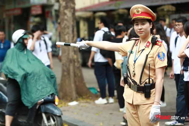 Nữ chiến sĩ CSGT điều tiết giao thông, đảm bảo cho các thí sinh không xảy ra sơ xuất trong kì thi quan trọng này.