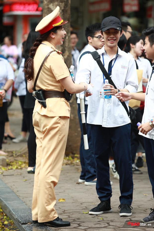 Nữ chiến sĩ CSGT phát nước cho các thí sinh, nụ cười luôn rạng rỡ trên khuôn mặt của các chiến sĩ khiến buổi thi chiều nay của các sĩ tử không còn quá áp lực.