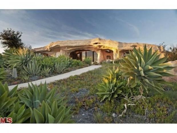 Căn nhà được đặt trên một ngọn đồi, bên ngoài trồng các loại cây hoang dã khá giống thời xa xưa.