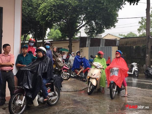Rất nhiều phụ huynh mặc áo mưa đứng đợi con em mình trước cổng trường.