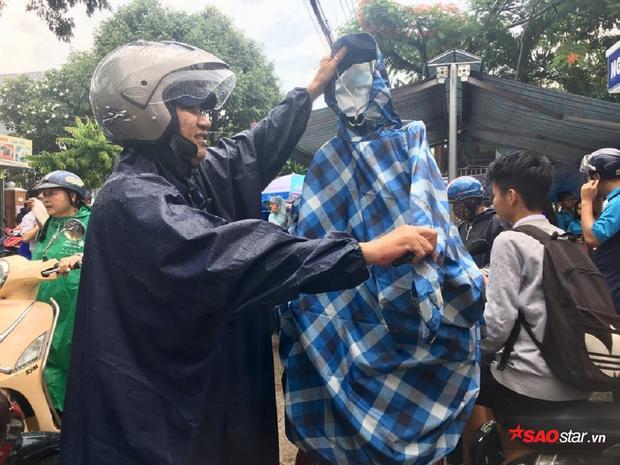 Một phụ huynh mang sẵn áo mưa cho con.
