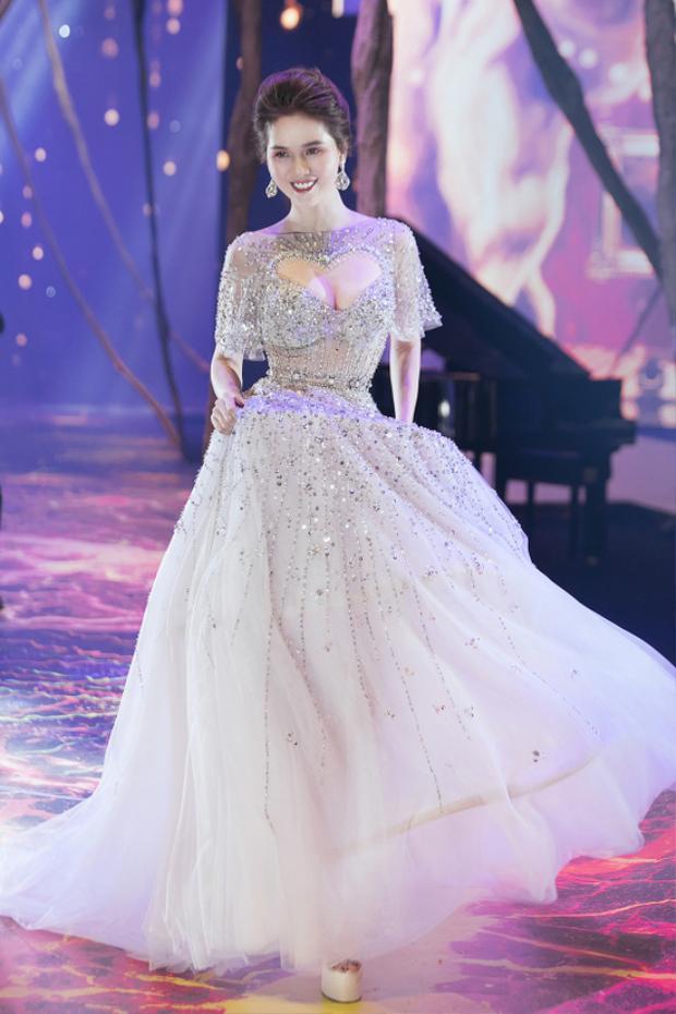 Ngọc Trinh mở màn xinh đẹp như 1 nàng công chúa. Thiết kế này gây chú ý với đường khoét sâu táo bạo hình trái tim khoe vòng 1 căng tràn của người mặc.