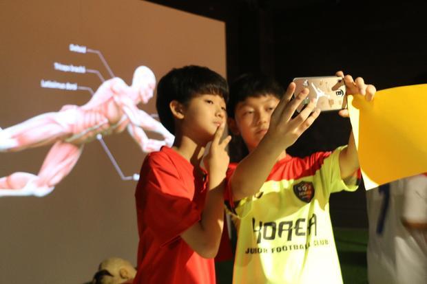Bạn nhỏ Hàn thích thú khám phá khả năng vận động của cơ thể và check-in tại phòng trưng bày cầu thủ.