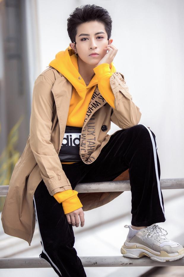 Tại set tiếp theo, Gil diện áo Hoodie vàng nghệ, bên ngoài khoác áo măng-tô màu nâu nhạt với điểm nhấn họa tiết nơi cổ áo.