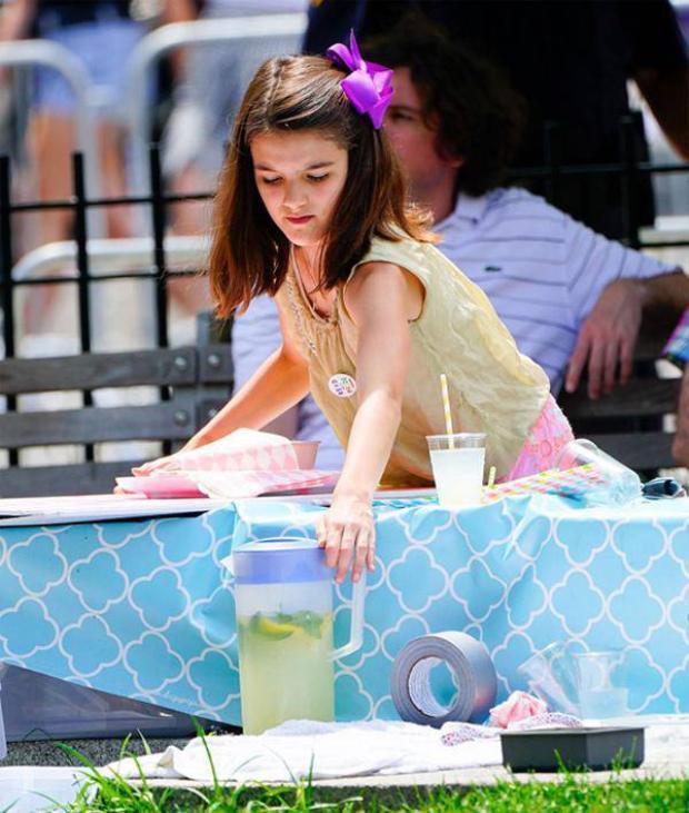 Hình ảnh Suri Cruise bán nước chanh ở ngoài đường.