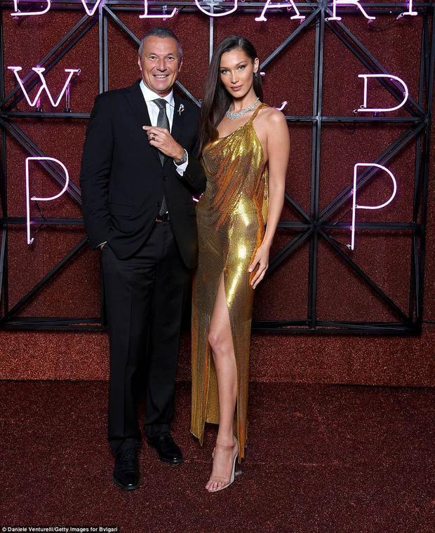 Bella Hadid diện bộ váy ánh vàng xẻ tà cao và hở lưng khoe vóc dáng chuẩn và chân dài gợi cảm.