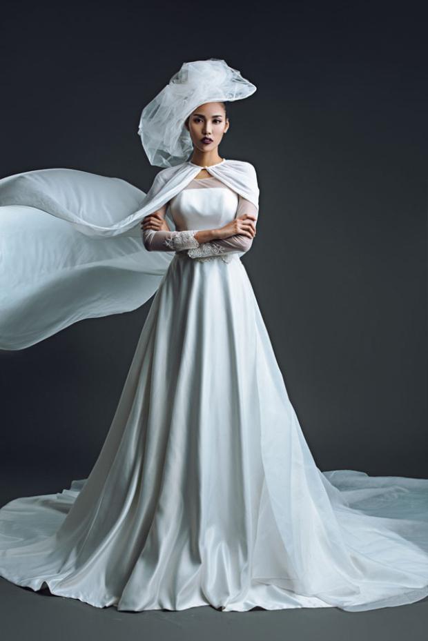 Đây là mẫu áo dài cưới cổ điển với một chút biến tấu cùng áo choàng dài mang lại vẻ quyền lực và khí chất cho chân dài.
