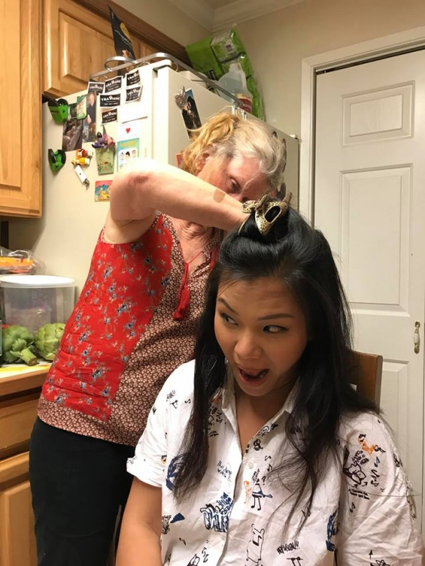 """Đây là biểu cảm của Phương Vy khi được mẹ chồng làm tóc cho. Trông cô nàng vô cùng hài hước nha. Thế nhưng, sự thật khiến nhiều người phải bật cười khi cô nàng chia sẻ rằng, do kéo nhau ra cánh đồng dạo chơi quay phim thì bị bọ chét dính vào tóc. Và đây là hình ảnh phải nhờ mẹ chồng bắt bọ chét dùm. Nàng ca sĩ của chúng ta hài hước đùa rằng """"cảm thấy bớt sang trọng nhiều lắm""""."""