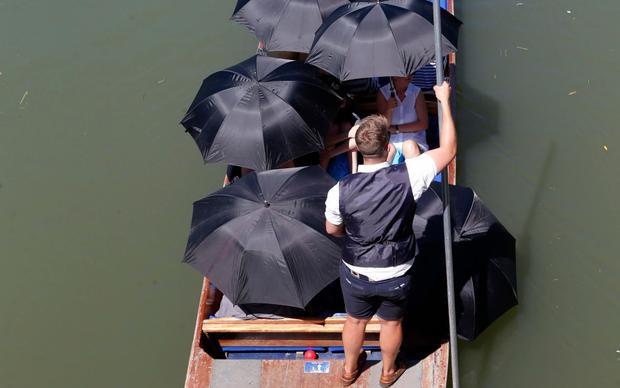 Du khách phải dùng đến những chiếc ô để che nắng khi đi thuyền dọc theo dòng sông Cam ở Cambridge. Ảnh: Splash News