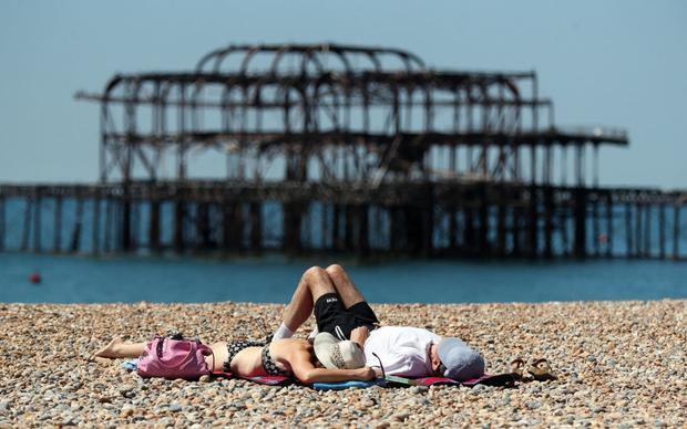 Người dân tranh thủ phơi mình dưới nắng tại bờ biển Brighton. Ảnh: Gareth Fuller
