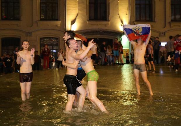 """Các anh chàng """"gấu Nga"""" cầm cờ, nhảy múa, ôm nhau trong đài phun nước."""