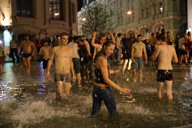 Không chỉ có nam giới, một cô gái cũng nhảy vào đài phun nước để chung vui.