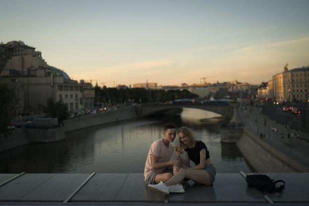 Cặp đôi ngồi xem điện thoại trên cây cầu ở thủ đô Moscow lúc hoàng hôn ngày 26/6.