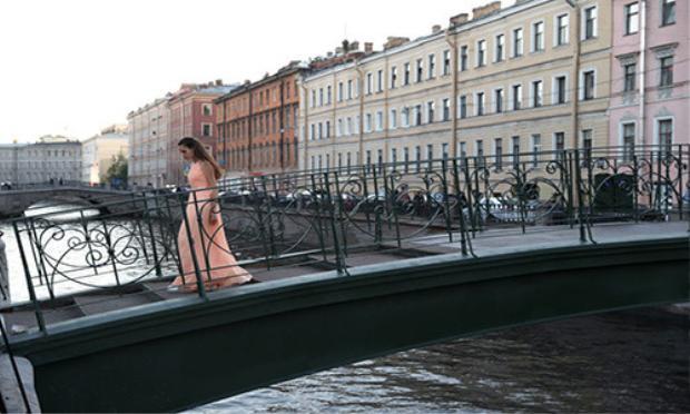 Người phụ nữ đi qua cây cầu ở thành phố St.Petersburg hôm 25/6.