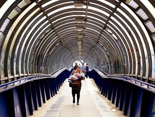 Một phụ nữ bế con đi qua cây cầu đi bộ ở Podolsk gần thủ đô Moscow ngày 19/6