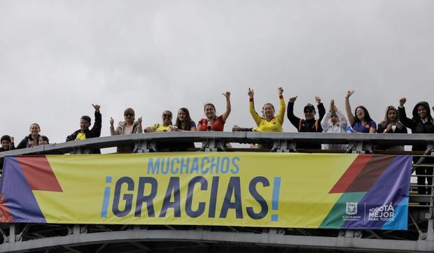 """Người dân mang khẩu hiệu với biểu ngữ """"Cám ơn các bạn rất nhiều"""" để chào đón những người hùng trong lòng họ trở về quê nhà. Những dòng chữ này trái ngược với những lời xúc phạm, đe dọa mà tuyển thủMateus Uribe và Carlos Bacca nhận được trên mạng xã hội khi họ đá hỏng trong loạt sút luân lưu."""