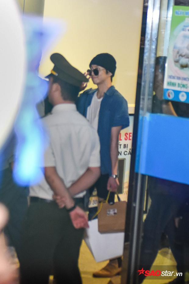 Seungyoon đeo kính đen, mỉm cười chào người hâm mộ.