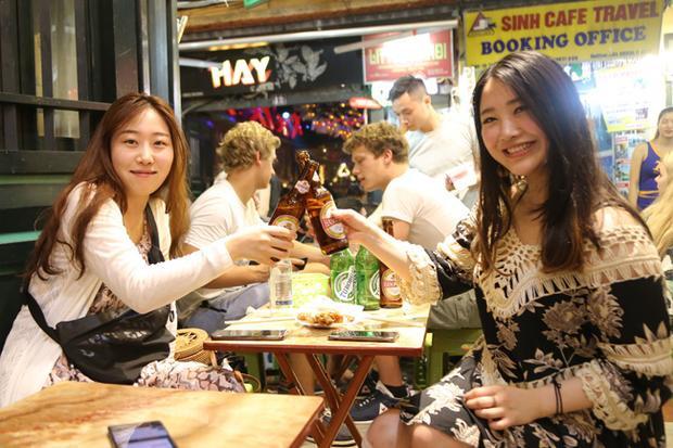 Cô Lee Sang Mi (bên phải), nữ du khách đến từ Hàn Quốc cho biết, tối nay rủ bạn ra Tạ Hiện uống bia để cổ vũ cho đội tuyển Hàn Quốc. Cô chia sẻ rằng được ngồi uống bia Việt Nam cùng bạn bè ở Tạ Hiện là trải nghiệm tuyệt vời.