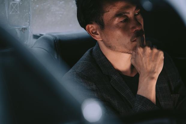 """Xuất hiện trong vai trò nam chính của MV, nhà thiết kế Trương Thanh Long với vẻ ngoài phong trần """"bụi bặm"""" cùng những đường nét nam tính trên gương mặt thật phù hợp để vào vai một người đàn ông mệt mỏi với một cuộc tình không còn nhiều cảm xúc."""