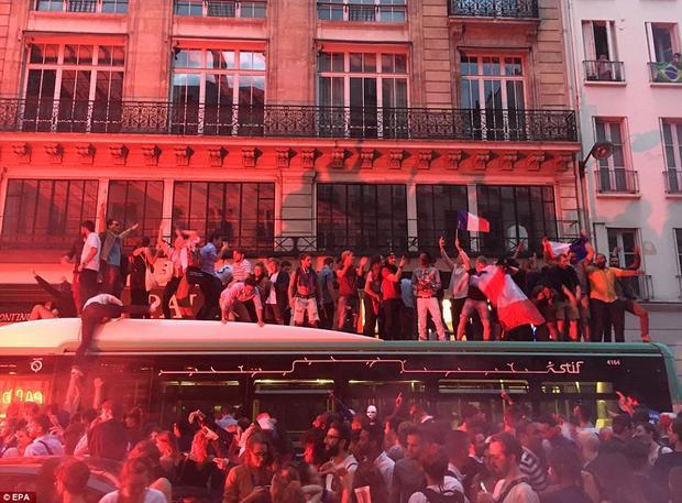"""Một đám đông cũng """"bắt chước"""" màn ăn mừng của các cổ động viên Anh khi trèo lên nóc xe buýt reo hò. Ảnh: EPA"""