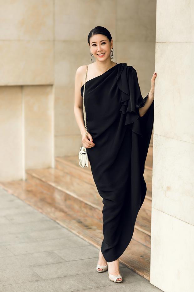 Với sắc đen trầm mặc, đơn giản, Hà Kiều Anh trở nên ấn tượng với dáng váy rộng, tạo phom bất đối xứng với những đường gấp nếp khéo léo ôm lấy những đường cong quyến rũ của người phụ nữ.