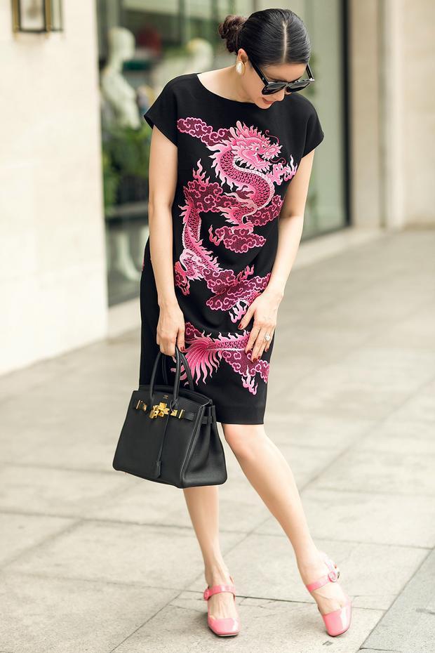 Mắt kính to bản, túi xách với tông màu đen được kết hợp hài hoà với bộ váy theo phong cách tối giản.
