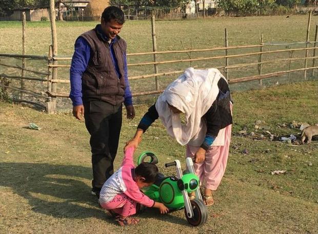 Vợ chồng anh Shahabuddin Ahmed và chị Salma Parbin vui đùa bên con trai Jonait dù đó không phải là người con chị sinh ra. Ảnh: BBC